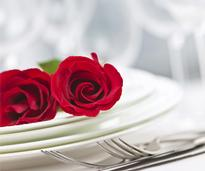 Table setting with red roses on plate