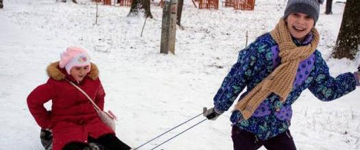 kid pulling other kid on sled