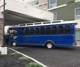 a blue trolley in front of a hotel