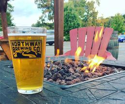 pint of beer sitting on a ledge next to a firepit