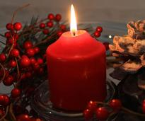 red candle by pinecone and red berries