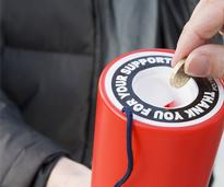 a hand putting a coin into a donation canister