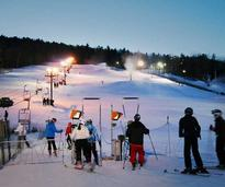 Skiiers approach the lift at West Mountain at night in Queensbury NY