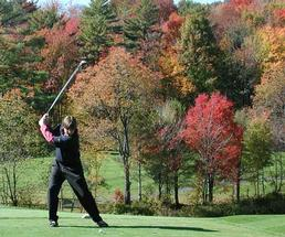 Man swinging golf ball with fall foliage in the background