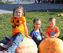 kids sitting on and near pumpkins