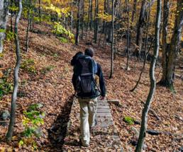back of guy hiking in the fall with backpack