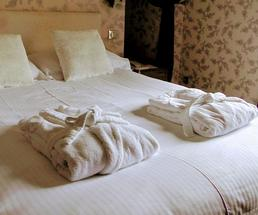 hotel bed with two bathrobes on it