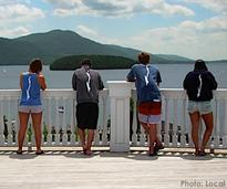 people looking at lake george wearing shirts with the shape of lake george on the back