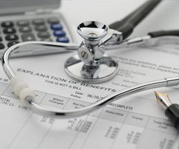 insurance statement, stethoscope, pen, and calculator