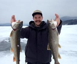 guy holding up fish on ice