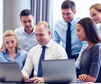 young businesspeople around a computer