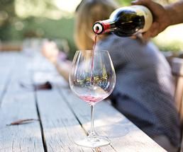 Red wine being poured into an empty glass on a picnic table