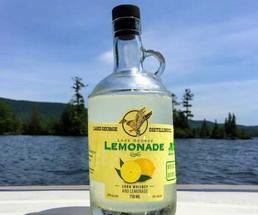 bottle of Lake George Lemonade whiskey in front of lake