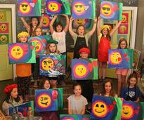 kids holding up paintings