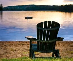 adirondack chair on a beach during sunset