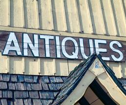 "sign on a building that says ""antiques"""