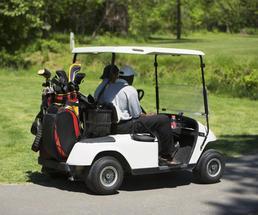 two men driving a golf cart