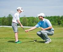 boy getting a lesson from a golf pro