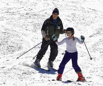Father and daughter downhill skiing