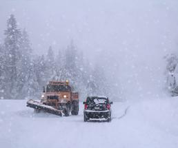 plow and car on a snowy road