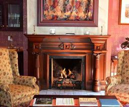 large fireplace near two chairs