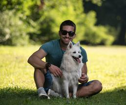 man sitting in the park with a white dog