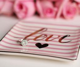 an engagement ring against a pink striped pad that says love