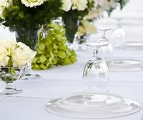 upside-down plate with upside-down glass on top, on a white tablecloth with white and green flowers on the table