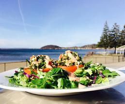 close up of a bowl of salad with a lake and blue sky in the background