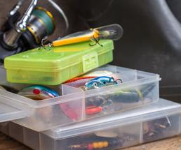 tackle boxes with fishing lures, a fishing reel, and a pair of boots