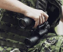 man in camouflage holding a pair of black binoculars