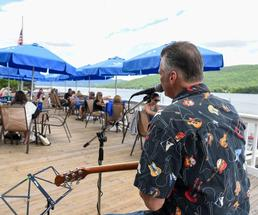 man playing guitar in front of a crowd of people sitting at tables next to the lake