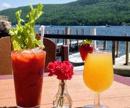 a bloody mary and a mimosa on a table in front of a lake