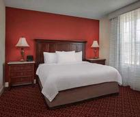 a hotel bedroom with white linens and a red wall