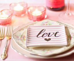 a plate with a napkin that says love, candles