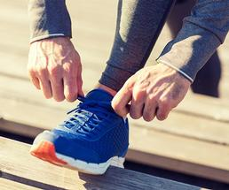 person tying a blue sneaker