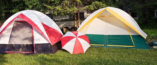 two tents and an umbrella with an rv in the background