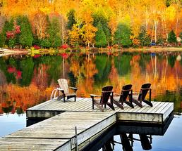 adirondack chairs on a dock with fall foliage in the background