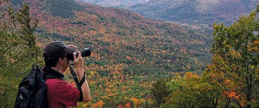 man taking pictures of fall foliage on a mountain