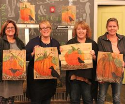 four women holding up paintings of pumpkins