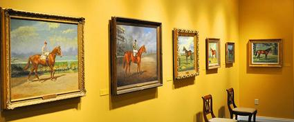 paintings of horses hung on a yellow wall