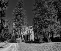 a black and white image of a mansion on a hill