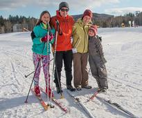 family of four with skis