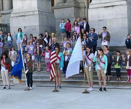 group of girl scouts having a ceremony on building steps