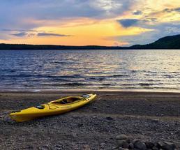 yellow kayak on a beach at sunset