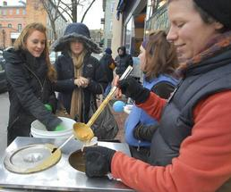 woman pouring chowder into cup