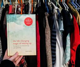Marie Kondo book held up in front of clothes in closet