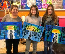 three women holding up paintings of winter scenes