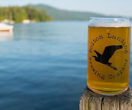 class of bolton landing brewing co. beer on a wood pillar in front of a lake