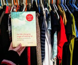 Marie Kondo book held up in front of closet